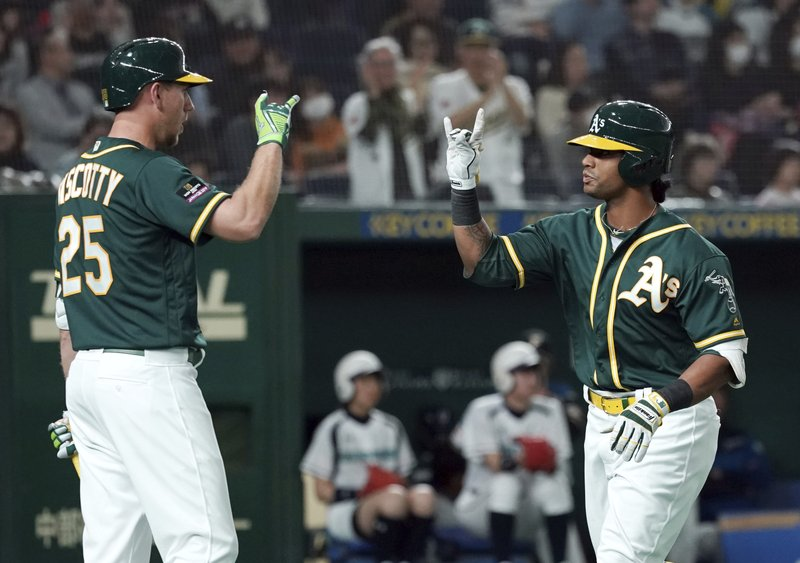 Oakland Athletics designated hitter Khris Davis, right, celebrates with his teammate Stephen Piscotty after hitting a grand slam off Nippon Ham Fighters pitcher Naoya Ishikawa in the ninth inning of their preseason exhibition baseball game at Tokyo Dome in Tokyo Monday, March 18, 2019. (AP Photo/Eugene Hoshiko)