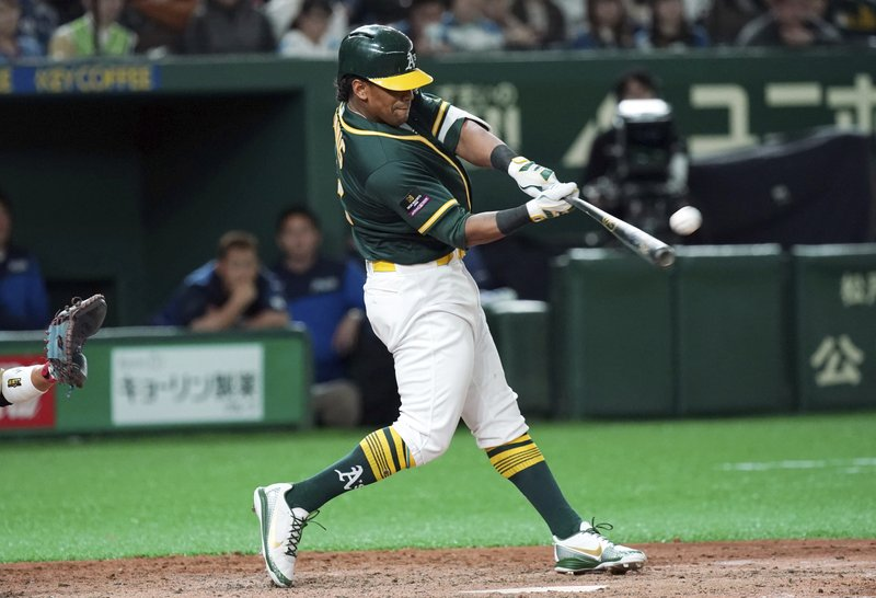 Oakland Athletics designated hitter Khris Davis hits a grand slam off Nippon Ham Fighters pitcher Naoya Ishikawa in the ninth inning of their preseason exhibition baseball game at Tokyo Dome in Tokyo Monday, March 18, 2019. (AP Photo/Eugene Hoshiko)
