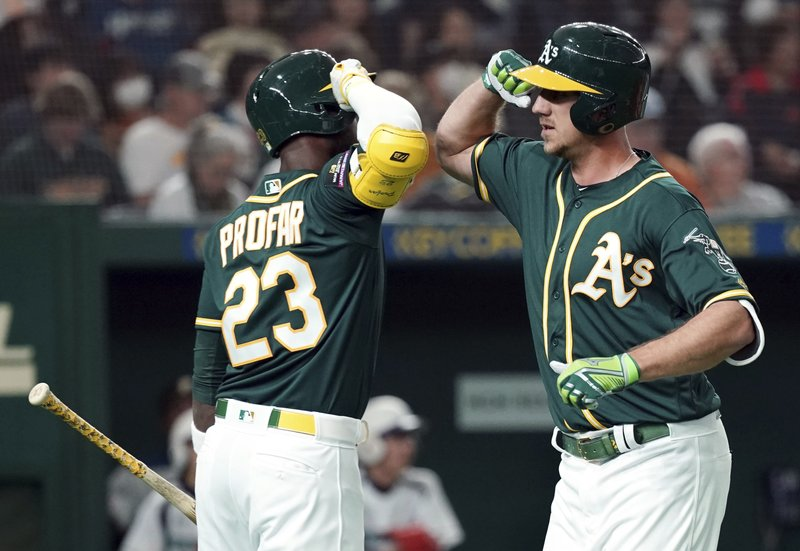 Oakland Athletics' Stephen Piscotty, right, celebrates with teammate Jurickson Profar (23) after hitting a solo home run off Nippon Ham Fighters starter Yuki Saito in the second inning of their pre-season exhibition baseball game at Tokyo Dome in Tokyo Monday, March 18, 2019. (AP Photo/Eugene Hoshiko)