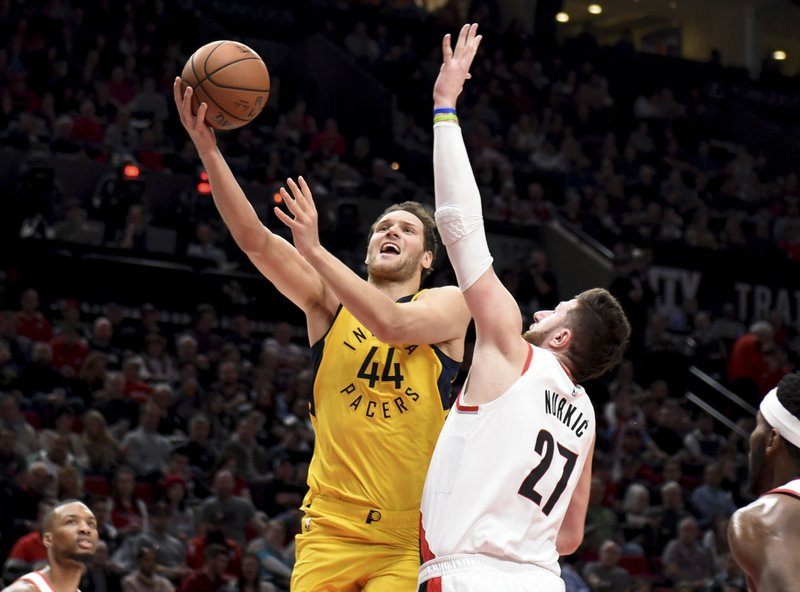 Indiana Pacers forward Bojan Bogdanovic, left, drives to the basket on Portland Trail Blazers center Jusuf Nurkic, right, during the first half of an NBA basketball game in Portland, Ore. (AP Photo/Steve Dykes)