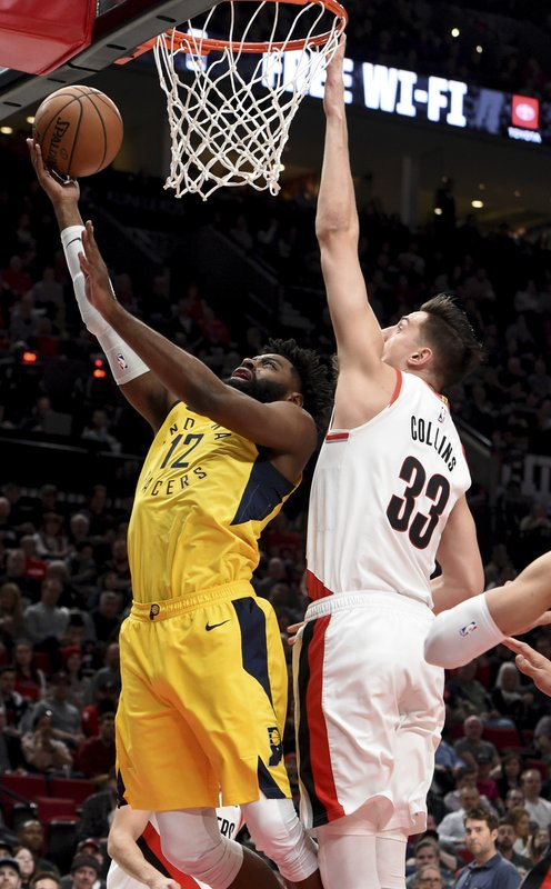 Indiana Pacers guard Tyreke Evans, left, drives to the basket on Portland Trail Blazers forward Zach Collins, right, during the first half of an NBA basketball game in Portland, Ore. (AP Photo/Steve Dykes)