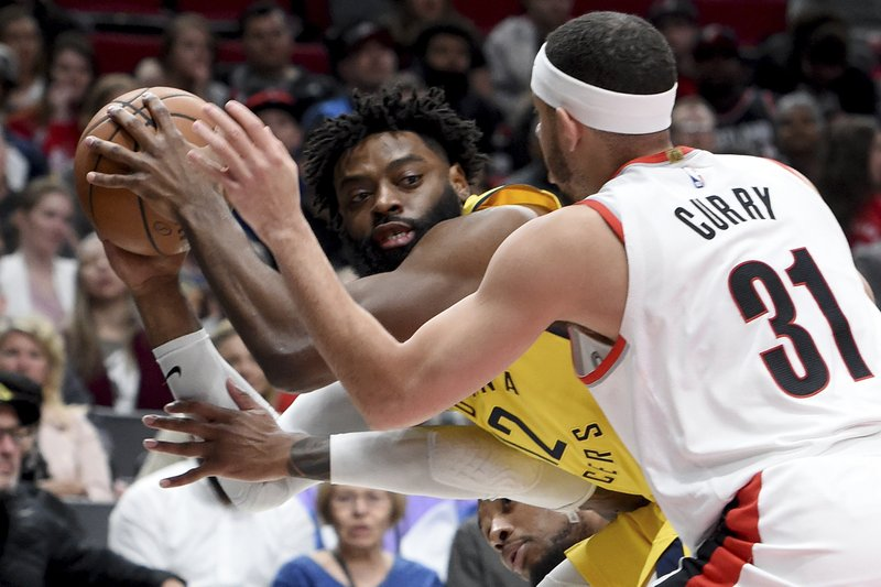 Indiana Pacers guard Tyreke Evans, left, looks to pass the ball as Portland Trail Blazers guard Seth Curry, right, defends during the first half of an NBA basketball game in Portland, Ore. (AP Photo/Steve Dykes)