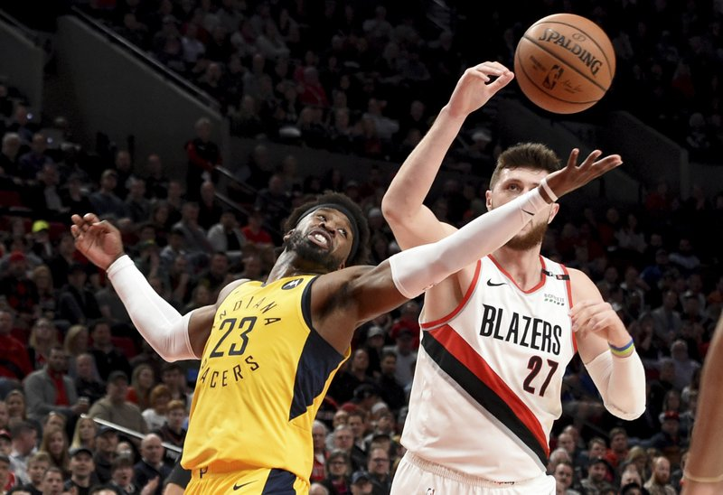 Indiana Pacers guard Wesley Matthews, left, battles for a rebound with Portland Trail Blazers center Jusuf Nurkic, right, during the first half of an NBA basketball game in Portland, Ore. (AP Photo/Steve Dykes)
