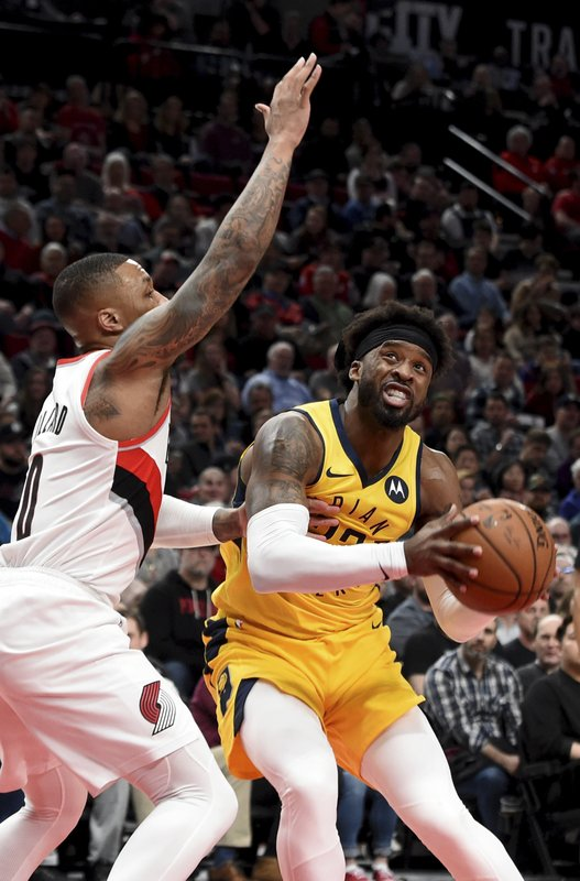 Indiana Pacers guard Wesley Matthews, right, drives to the basket against Portland Trail Blazers guard Damian Lillard, left, during the first half of an NBA basketball game in Portland, Ore. (AP Photo/Steve Dykes)