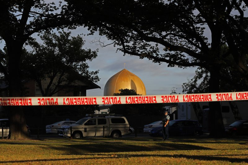 A police officer stands guard in front of the Masjid Al Noor mosque in Christchurch, New Zealand, Sunday, March 17, 2019, where one of two mass shootings occurred. (AP Photo/Vincent Yu)