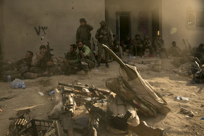 U.S.-backed Syrian Democratic Forces (SDF) fighters rest after returning from the front line after territorial gains over Islamic State militants in Baghouz, Syria, Tuesday, March 19, 2019. (AP Photo/Maya Alleruzzo)