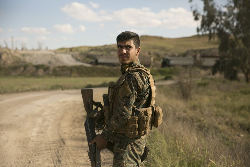 A U.S.-backed Syrian Democratic Forces (SDF) fighter stands guard as trucks carrying Islamic State militants and families who surrendered in Baghouz, Syria, move to a camp Tuesday, March 19, 2019. (AP Photo/Maya Alleruzzo)