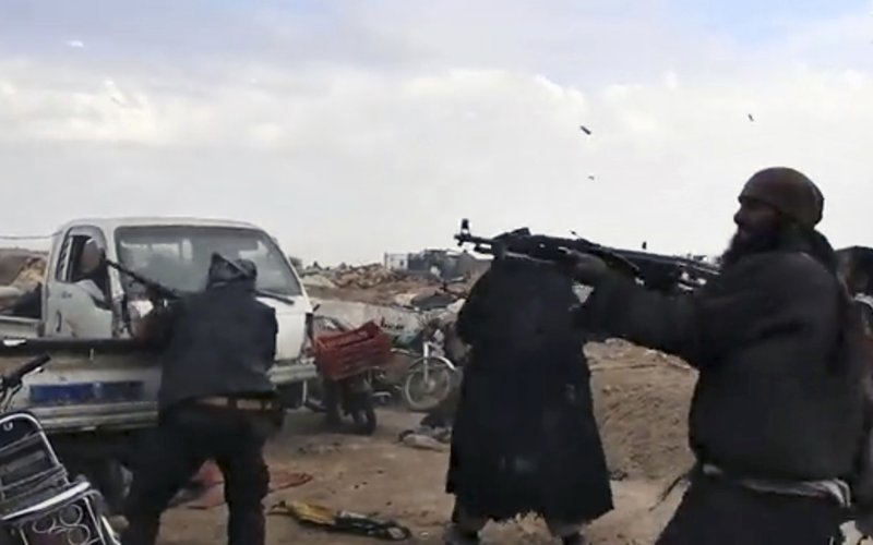 This frame grab from video posted online Monday, March 18, 2019, by the Aamaq News Agency, a media arm of the Islamic State group, shows Islamic State fighters firing their weapons during clashes with the U. (SDF) fighters, in Baghouz, the Islamic State group's last pocket of territory in Syria. U.S.-backed Syrian forces fighting the Islamic State group announced Tuesday they have taken control over an encampment in an eastern Syrian village where IS militants have been besieged for months, refusing to surrender. (Aamaq News Agency via AP)