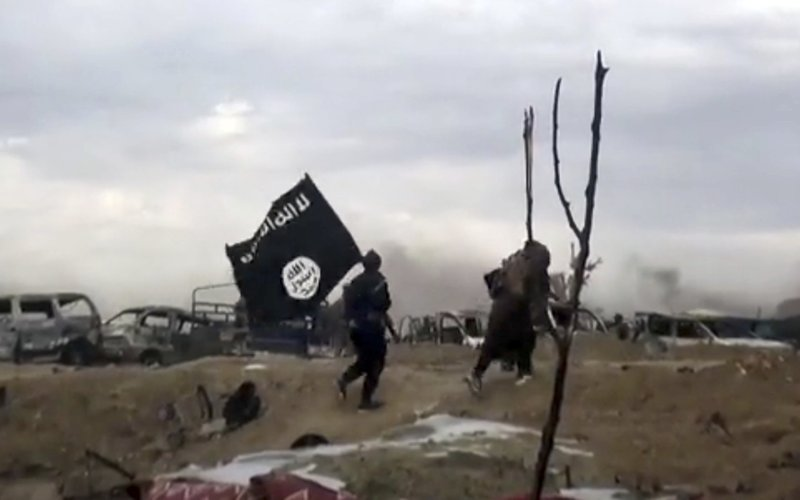 This frame grab from video posted online Monday, March 18, 2019, by the Aamaq News Agency, a media arm of the Islamic State group, shows IS fighters walking as they hold the group's flag inside Baghouz, the Islamic State group's last pocket of territory in Syria. (Aamaq News Agency via AP)