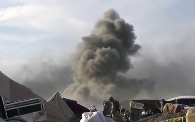 This frame grab from video posted online Monday, March 18, 2019, by the Aamaq News Agency, a media arm of the Islamic State group, shows smoke rising as an IS fighter walking inside Baghouz, the Islamic State group's last pocket of territory in Syria. (Aamaq News Agency via AP)
