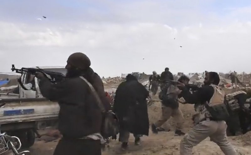This frame grab from video posted online Monday, March 18, 2019, by the Aamaq News Agency, a media arm of the Islamic State group, shows IS fighters firing their weapons during clashes with the U. (SDF) fighters, in Baghouz, the IS group's last pocket of territory in Syria. U.S.-backed Syrian forces fighting the Islamic State group announced Tuesday they have taken control over an encampment in an eastern Syrian village where IS militants have been besieged for months, refusing to surrender. (Aamaq News Agency via AP)