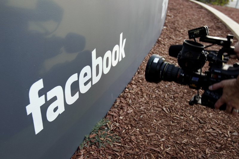 FILE- In this May 18, 2012, file photo a television photographer shoots the sign outside of Facebook headquarters in Menlo Park, Calif. (AP Photo/Paul Sakuma, File)