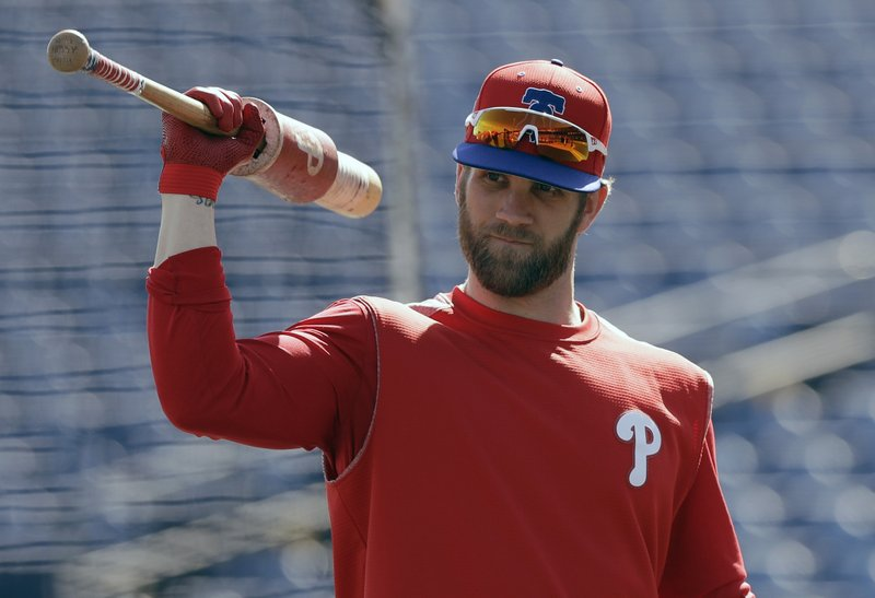 FILE - In this March 9, 2019 file photo Philadelphia Phillies' Bryce Harper waits his turn in the batting cage before a spring training baseball game against the Toronto Blue Jays in Clearwater, Fla. (AP Photo/Chris O'Meara, file)