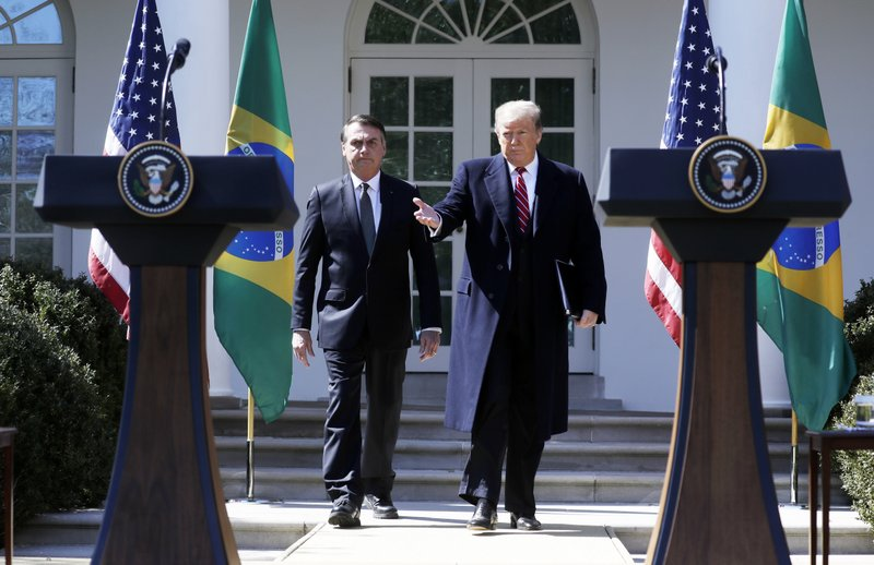 President Donald Trump and Brazilian President Jair Bolsonaro walk out to the Rose Garden at the White House for a news conference, Tuesday, March 19, 2019, in Washington. (AP Photo/Evan Vucci)