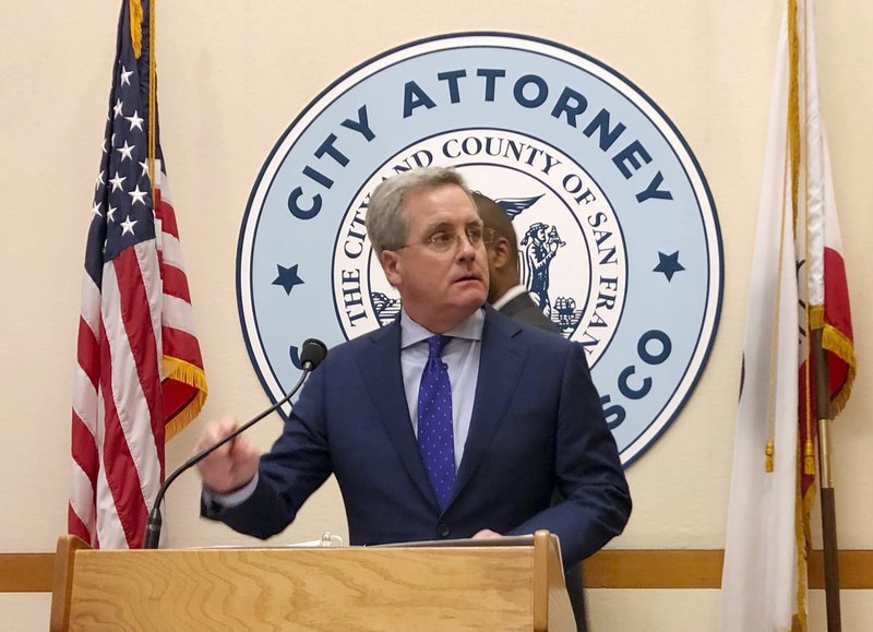 San Francisco City Attorney Dennis Herrera announces that he's cracking down on the sale of e-cigarettes that he says aggressively target youth, at a City Hall news conference Tuesday, March 19, 2019. (AP Photo/Janie Har)