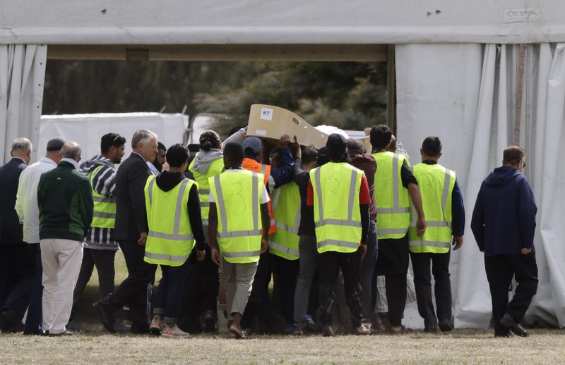 Mourners carry the body of a victim of the Friday March 15 mosque shootings for a burial at the Memorial Park Cemetery in Christchurch, New Zealand, Wednesday, March 20, 2019. (AP Photo/Mark Baker)