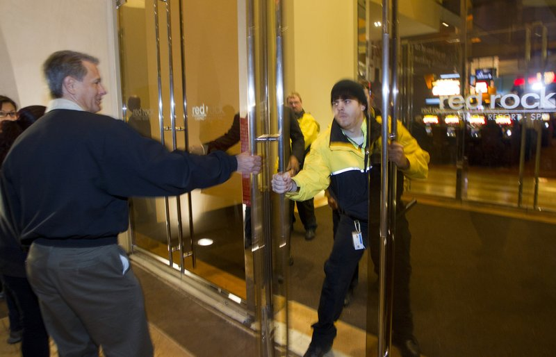 FILE - In this Dec. 11, 2014 file photo, a security officer closes a door on Culinary Union Local 226 President Ted Pappageorge during a union protest at Station Casino's Red Rock Resort in Las Vegas. (Steve Marcus/Las Vegas Sun via AP, File)