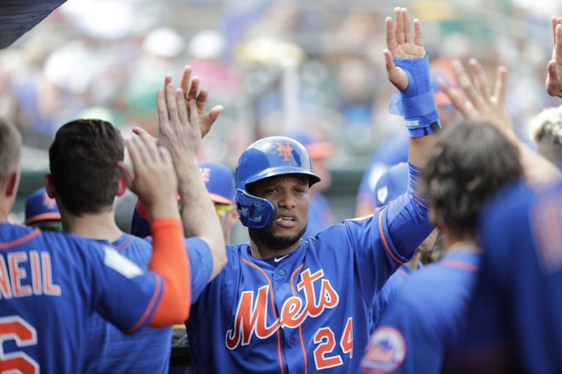 FILE - In this March 16, 2019, file photo, New York Mets' Robinson Cano (24) celebrates in the dugout with his teammates after scoring in the third during an exhibition spring training baseball game against the Miami Marlins in Jupiter, Fla. (AP Photo/Brynn Anderson, File)