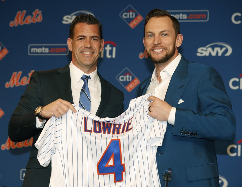 FILE - In this Jan. 16, 2019, file photo, New York Mets general manager Brodie Van Wagenen, left, poses for a photograph with new infielder Jed Lowrie during a baseball news conference in New York. (AP Photo/Kathy Willens, File)