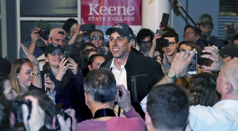 Former Texas congressman Beto O'Rourke smiles as he is surrounded while arriving for a campaign stop at Keene State College in Keene, N. (AP Photo/Charles Krupa)