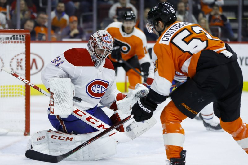 Montreal Canadiens' Carey Price, left, blocks a shot by Philadelphia Flyers' Shayne Gostisbehere, right, during the second period of an NHL hockey game, Tuesday, March 19, 2019, in Philadelphia. (AP Photo/Matt Slocum)