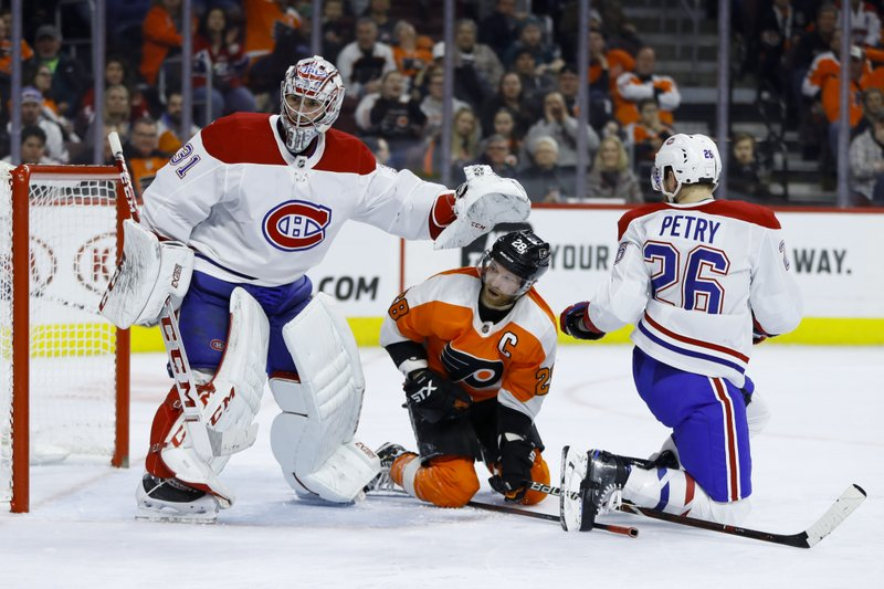 Philadelphia Flyers' Claude Giroux, center, gets a shove from Montreal Canadiens' Carey Price, left, after a collision with Jeff Petry during the second period of an NHL hockey game, Tuesday, March 19, 2019, in Philadelphia. (AP Photo/Matt Slocum)