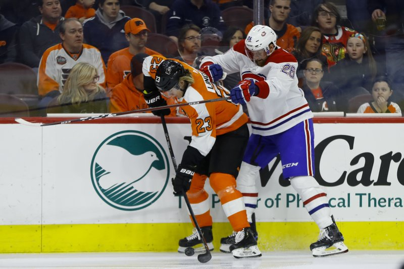 Philadelphia Flyers' Oskar Lindblom, left, and Montreal Canadiens' Jeff Petry battle for the puck during the first period of an NHL hockey game, Tuesday, March 19, 2019, in Philadelphia. (AP Photo/Matt Slocum)