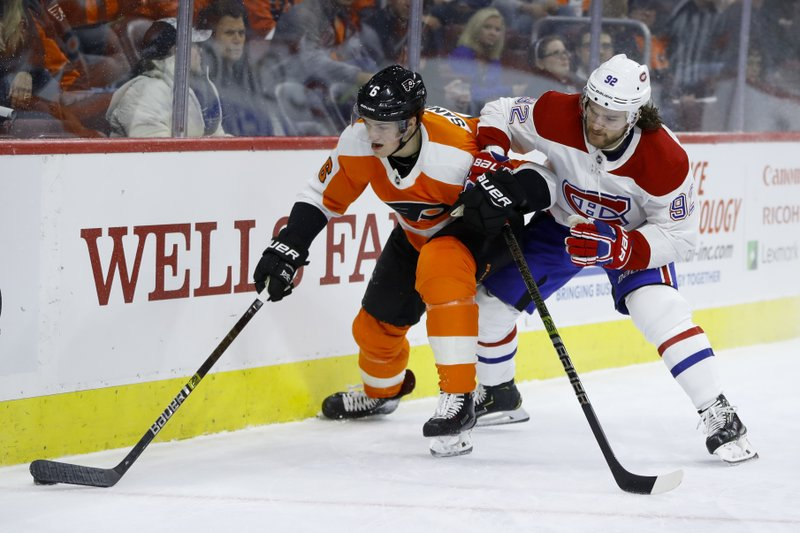 Philadelphia Flyers' Travis Sanheim, left, and Montreal Canadiens' Jonathan Drouin battle for the puck during the first period of an NHL hockey game, Tuesday, March 19, 2019, in Philadelphia. (AP Photo/Matt Slocum)