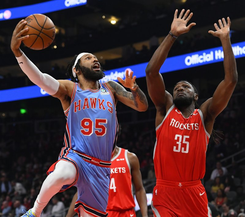 Atlanta Hawks forward DeAndre' Bembry (95) shoots as the Houston Rockets forward Kenneth Faried defends during the first quarter of an NBA basketball game Tuesday, March 19, in Atlanta. (AP Photo/John Amis)