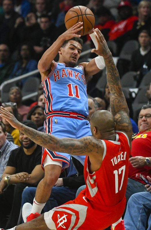 Atlanta Hawks guard Trae Young (11) and Houston Rockets forward P.J Tucker vie for a loose ball during the first quarter of an NBA basketball game Tuesday, March 19, in Atlanta. (AP Photo/John Amis)