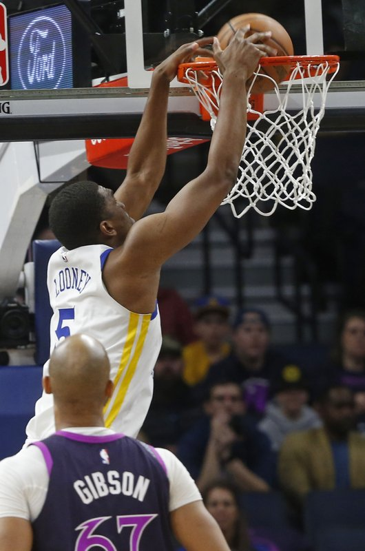 Golden State Warriors' Kevon Looney dunks against the Minnesota Timberwolves in the first half of an NBA basketball game Tuesday, March 19, 2019, in Minneapolis. (AP Photo/Jim Mone)