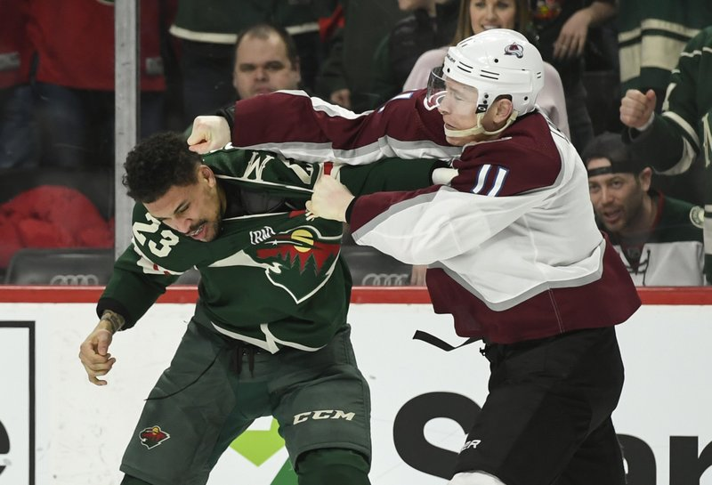 Minnesota Wild right wing J.T. Brown (23) and Colorado Avalanche right wing Matt Calvert (11) both receive major penalty minutes for their fight during the second period of an NHL hockey game Tuesday, March 19, 2019, in St. (AP Photo/Craig Lassig)