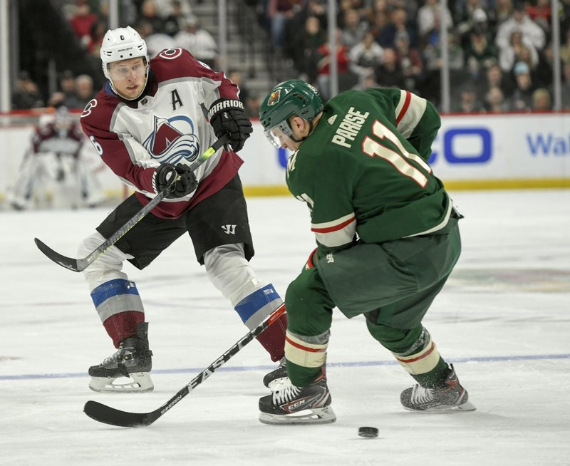 Colorado Avalanche defenseman Erik Johnson, left, takes a shot on goal past Minnesota Wild left wing Zach Parise during the second period of an NHL hockey game Tuesday, March 19, 2019, in St. (AP Photo/Craig Lassig)