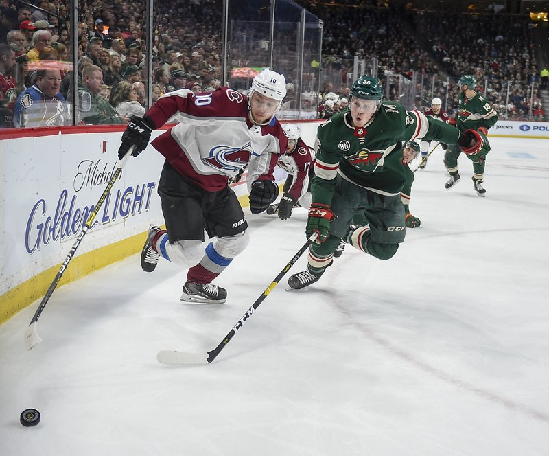 Colorado right wing Sven Andrighetto, left and Minnesota Wild defenseman Nick Seeler race to the puck during the second period of an NHL hockey game Tuesday, March 19, 2019, in St. (AP Photo/Craig Lassig)