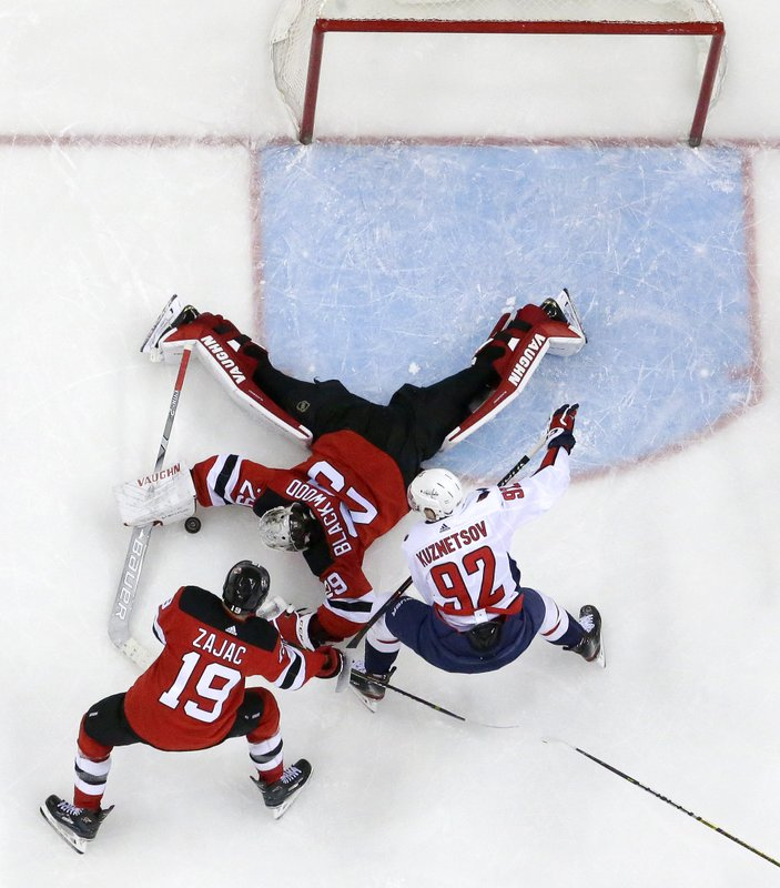New Jersey Devils goaltender MacKenzie Blackwood (29) dives to make a save against Washington Capitals center Evgeny Kuznetsov (92), of Russia, during the third period of an NHL hockey game, Tuesday, March 19, 2019, in Newark, N. (19) helps defend on the play. The Capitals won 4-1. (AP Photo/Julio Cortez)