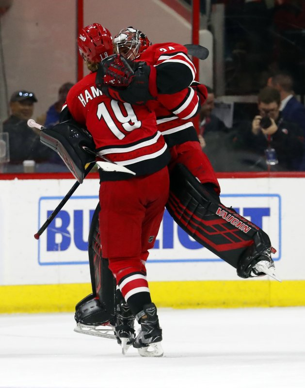 Carolina Hurricanes goaltender Petr Mrazek (34) celebrates his win over the Pittsburgh Penguins with teammate Dougie Hamilton (19) during the third period of an NHL hockey game, Tuesday, March 19, 2019, in Raleigh, N. (AP Photo/Karl B DeBlaker)