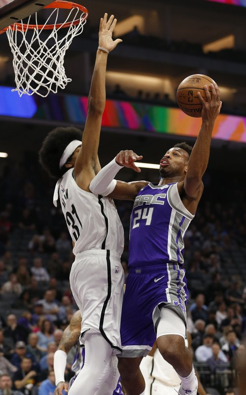 Sacramento Kings guard Buddy Hield, right, goes to the basket against Brooklyn Nets center Jarrett Allen, left, during the first quarter of an NBA basketball game Tuesday, March 19, 2019, in Sacramento, Calif. (AP Photo/Rich Pedroncelli)