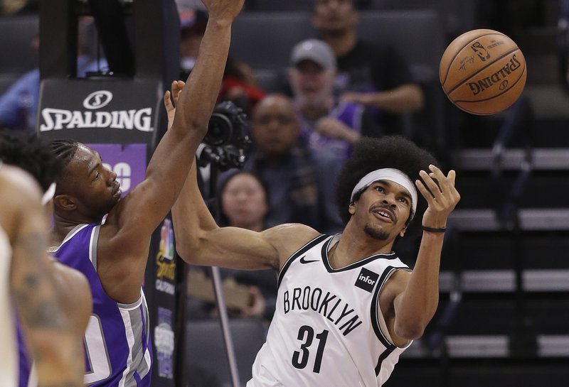 Brooklyn Nets center Jarrett Allen, right, reaches for a rebound as Sacramento Kings forward Harry Giles III, left, looks on during the first quarter of an NBA basketball game Tuesday, March 19, 2019, in Sacramento, Calif. (AP Photo/Rich Pedroncelli)