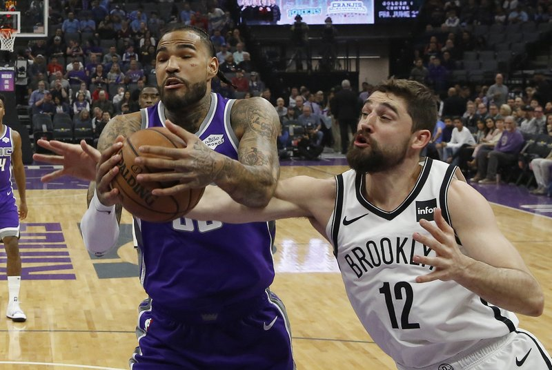 Sacramento Kings center Willie Cauley-Stein, left, and Brooklyn Nets forward Joe Harris, right, battle for the ball during the first quarter of an NBA basketball game Tuesday, March 19, 2019, in Sacramento, Calif. (AP Photo/Rich Pedroncelli)
