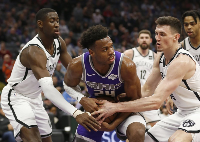 Sacramento Kings guard Buddy Hield, center, is double-teamed by Brooklyn Nets' Caris LeVert, left, and Rodions Jurucs, right, during the first quarter of an NBA basketball game Tuesday, March 19, 2019, in Sacramento, Calif. (AP Photo/Rich Pedroncelli)