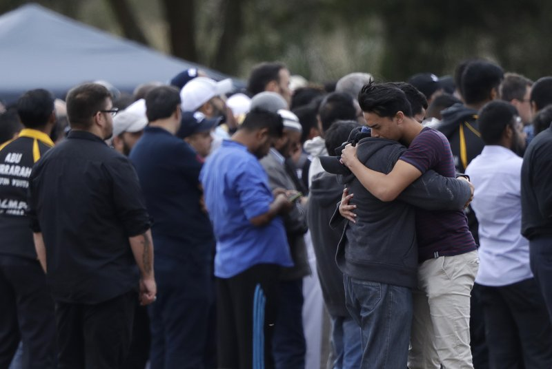 Mourners react during a burial for a victim of the March 15 mosque shootings at the Memorial Park Cemetery in Christchurch, New Zealand, Wednesday, March 20, 2019. (AP Photo/Mark Baker)