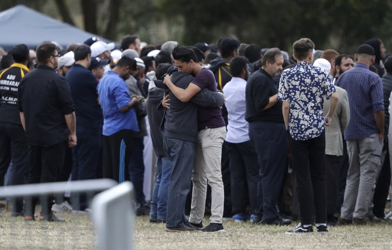 Mourners react as they carry the body of a victim of Friday March 15 mosque shootings for a burial at the Memorial Park Cemetery in Christchurch, New Zealand, Wednesday, March 20, 2019. (AP Photo/Mark Baker)