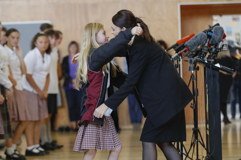 New Zealand's Prime Minister Jacinda Ardern, right, hugs and consoles a student during a high school visit in Christchurch, New Zealand, Wednesday, March 20, 2019. (AP Photo/Vincent Thian)
