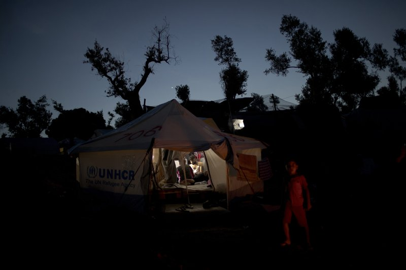 FILE - In this Tuesday, May 2, 2018 file photo, a Syrian family sit inside a tent at a makeshift camp outside Moria on the northeastern Aegean island of Lesbos, Greece. (AP Photo/Petros Giannakouris, File)