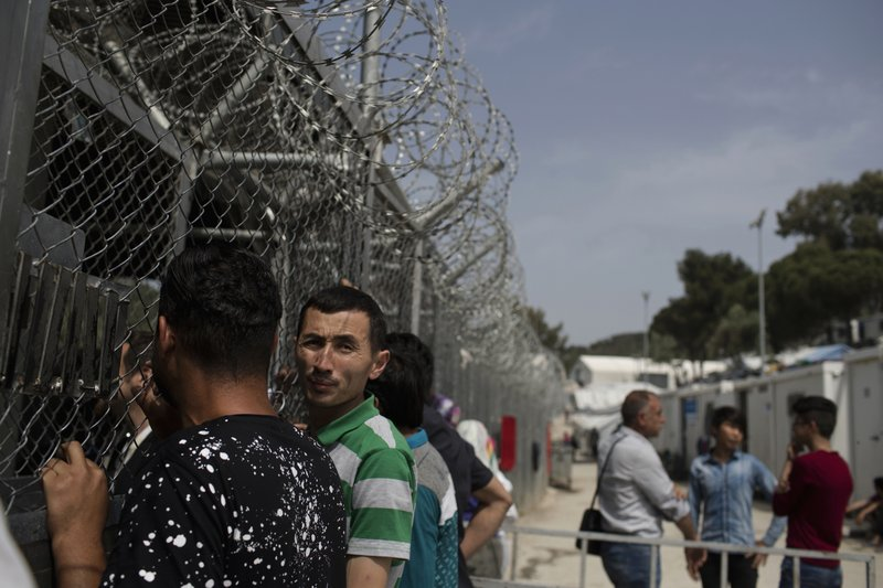 FILE - In this Friday, May 4, 2018 file photo, migrants and refugees wait outside the European Asylum Support Service offices inside the camp of Moria on the northeastern Aegean island of Lesbos, Greece. (AP Photo/Petros Giannakouris, File)