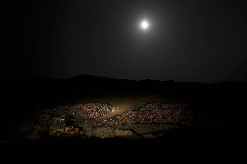 FILE - In this early Saturday May 5, 2018 file photo, the moon rises above piles of discarded life vests and dinghies used by migrants and refugees crossing from the nearby Turkish coast, at a dump on the Greek island of Lesbos. (AP Photo/Petros Giannakouris, File)