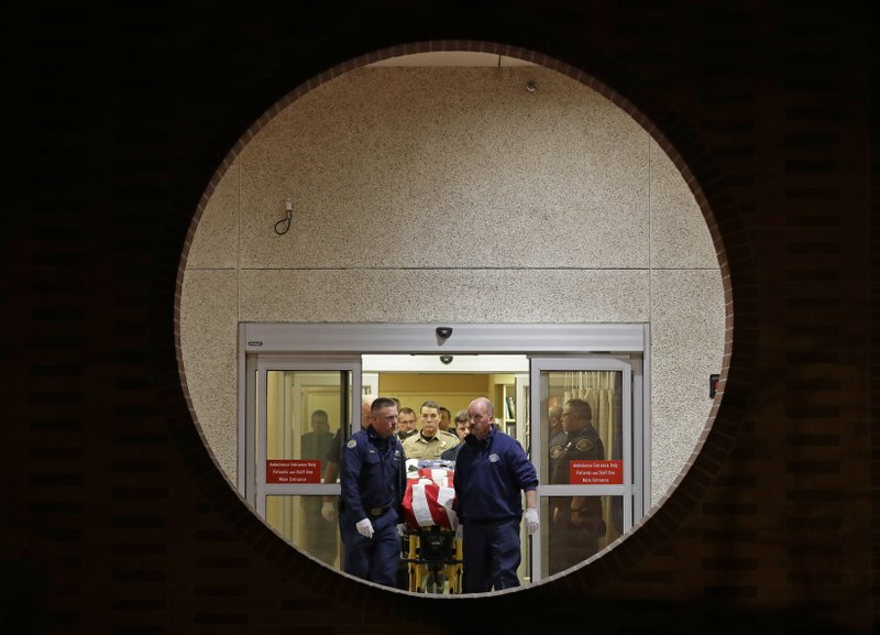 The body of a Kittitas County Sheriff's deputy is draped with a U.S. flag as it is carried out of Kittitas Valley Healthcare Hospital in the early morning hours of Wednesday, March 20, 2019, in Ellensburg, Wash. (AP Photo/Ted S. Warren)