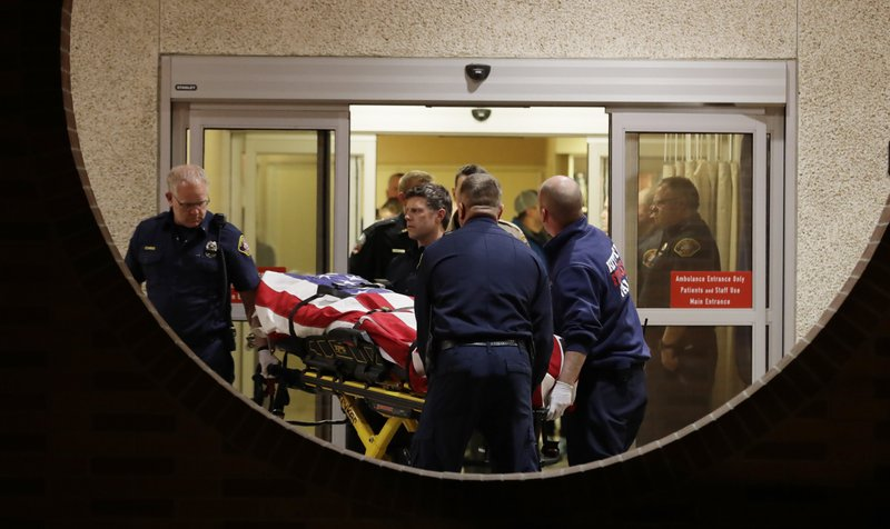 The body of a Kittitas County Sheriff's deputy is draped with a U.S. flag as it is carried out of Kittitas Valley Healthcare Hospital, in the early morning hours of Wednesday, March 20, 2019, in Ellensburg, Wash. (AP Photo/Ted S. Warren)