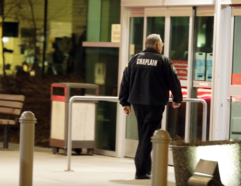 A law enforcement chaplain walks into Kittitas Valley Healthcare Hospital, in the late night hours of Tuesday, March 19, 2019, in Ellensburg, Wash. (AP Photo/Ted S. Warren)