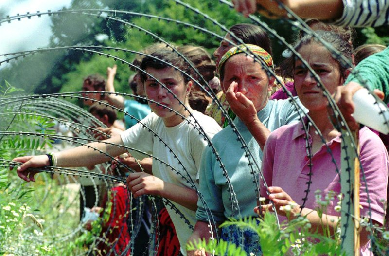 FILE - A July 13, 1995 file photo shows refugees from the overrun U.N. safe haven enclave of Srebrenica looking through the razor-wire at newly arriving refugees, in a UN base 12 kms south of Tuzla, 100kms (60 miles) north of Sarajevo. (AP Photo/Darko Bandic, File)